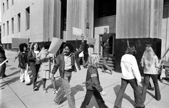 Group of young people carry picket signs in front of the Federal Building in Detroit, Michigan to protest busing on May 6, 1975.