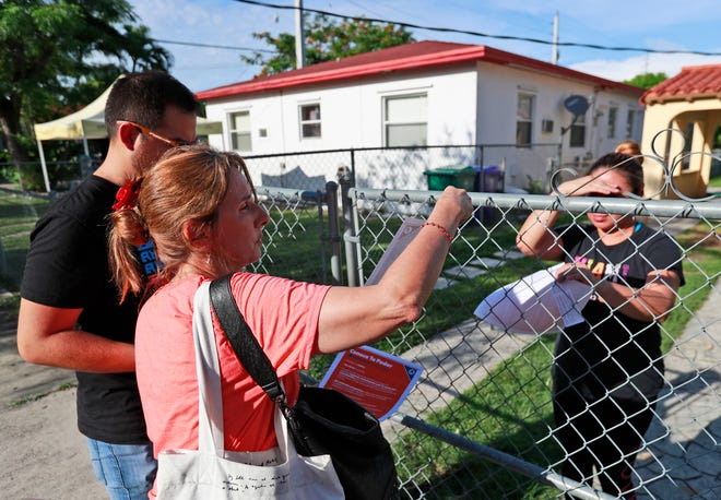 Immigration advocates Maria Bilbao, foreground, and Roberto Wong, left, both with United We Dream, go house-to-house handing out flyers, Thursday, July 11, 2019, in the Little Havana neighborhood in Miami.