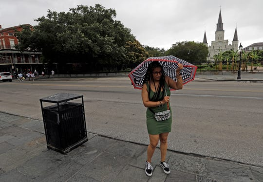 Brittany Fletcher holds onto her umbrella near Jackson Square as winds blow Friday, July 12, 2019, in New Orleans.