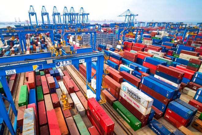 In this Tuesday, May 14, 2019, photo, containers are piled up at a port in Qingdao in east China's Shandong province. China's imports from the United States plunged 31.4% in June from a year earlier amid a tariff war with Washington, while exports to the U.S. market sank 7.8%, Customs data showed Friday, July 12, 2019.