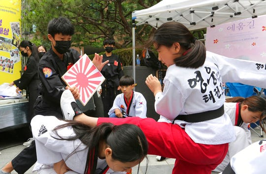A South Korean elementary school student kicks a wooden plate showing a Japanese rising sun flag during a rally demanding full compensation and an apology for wartime sex slaves from the Japanese government in front of the Japanese embassy in Seoul, South Korea, Wednesday, July 10, 2019.
