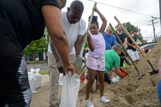 Nyla Trepagnier, center, fills a sandbag held by her grandparents Heloise and Ronald Nelson, left, at a sandbag station provided by local bar the Mid-City Yacht Club in New Orleans, La. Friday, July 12, 2019.