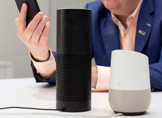 An Amazon Echo, center, and a Google Home, right.