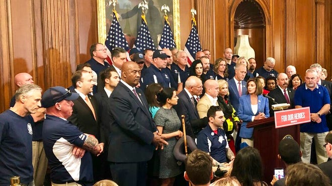 House Speaker Nancy Pelosi speaks at a news conference on behalf of 9/11 victims and families, Friday, July 12, 2019, at the Capitol in Washington. The House is expected to approve a bill Friday ensuring that a victims' compensation fund for the Sept. 11 attacks never runs out of money. Entertainer and activist Jon Stewart, listens at left.