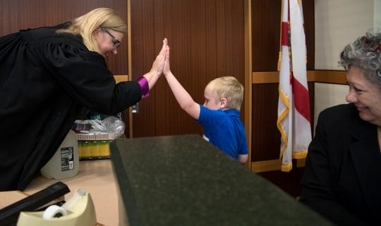 20th Judicial Circuit Judge Carolyn Swift celebrates with Lucas Bechler, 7, after he and his two brothers were adopted on Thursday at the Lee County Justice Complex Center in downtown Fort Myers. The brothers were adopted by Michele and David Bechler.
