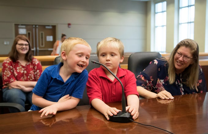 """""""I want to be adopted,"""" Lucas Bechler, 7, left, tells 20th Judicial Circuit Judge Carolyn Swift on Thursday during an adoption hearing at the Lee County Justice Complex Center in downtown Fort Myers. Lucas and his brothers, Jacob, 8, center, and Matthew, 13, (not pictured) were adopted by Michele Bechler, right, and her husband David."""