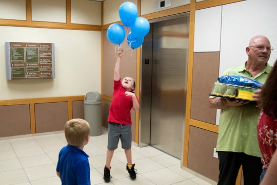 Jacob Bechler, 8, center, celebrates being adopted on Thursday at the Lee County Justice Complex Center in downtown Fort Myers. Jacob and his two brothers were adopted by Michele and David Bechler.