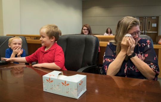 Michele Bechler, right, celebrates after adopting Lucas, 7, left, and his brothers, Jacob, 8, center, and Matthew, 13, (not pictured) during an adoption hearing at the Lee County Justice Complex Center in downtown Fort Myers.