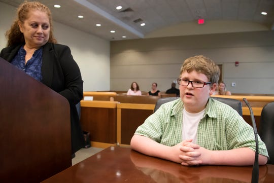 """We want to be with them,"" Matthew Bechler, 13, right, tells 20th Judicial Circuit Judge Carolyn Swift on Thursday during an adoption hearing at the Lee County Justice Complex Center in downtown Fort Myers. Matthew and his brothers, Jacob, 8, and Lucas, 7, were adopted by Michele and David Bechler. Attorney Theresa Daniels, left, assisted the Bechlers."