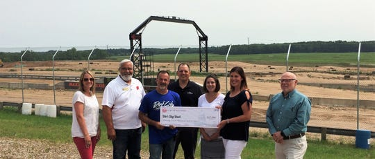The Wisconsin Department of Tourism on July 8 donated $27,000 to the Lena Motorsports Club to promote the inaugural Dirt City Duel on July 27-28 at the new Dirt City Motorplex at Lena. The money is Joint Effort Marketing grant, will help pay for print, broadcast, outdoor and social media advertising to promote the race to attendees from Wisconsin, Minnesota, Michigan and Canada. The event is expected to attract 160 racers and 16,500 spectators to the area, generating an estimated $856,000 in visitor spending. Holding the ceremonial check are Lena Motorsports Club president Don Demeny and board member Stephanie Paitl. From left on the spectator hill are Ashley Bahrke of Oconto County Economic Development Corp., Rep. Jeff Mursau, Demeny, Jeff Anderson of the Department of Tourism, Samantha Boucher and Paul Ehrfurth, both of OCEDC. The event is expected to attract 160 racers and 16,500 spectators to the area, generating an estimated $856,000 in visitor spending, according the state tourism department.