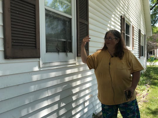 Karen Williams points to bullet damage to her house on 14th Avenue from a drive-by shooting Thursday night. Three Green Bay teens were arrested in connection to the shooting.