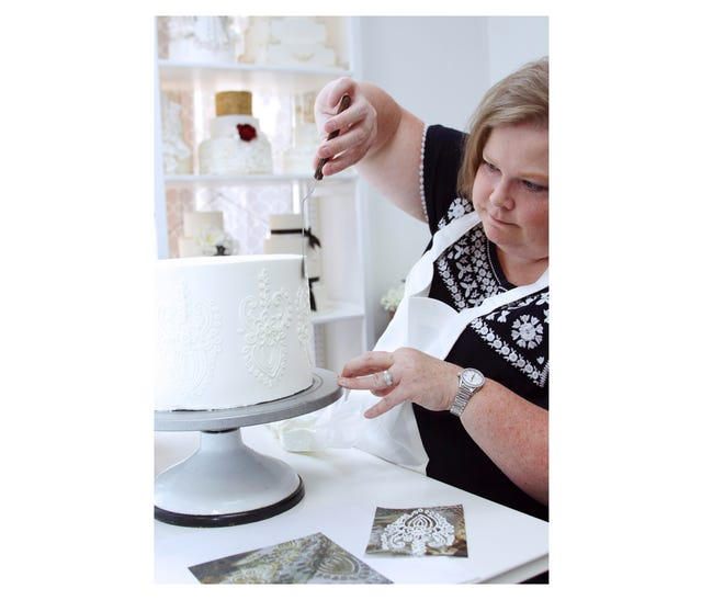 Susan McMakin, owner of Couture Cakes, replicates the intricate lace design from the bride's dress onto the wedding cake.