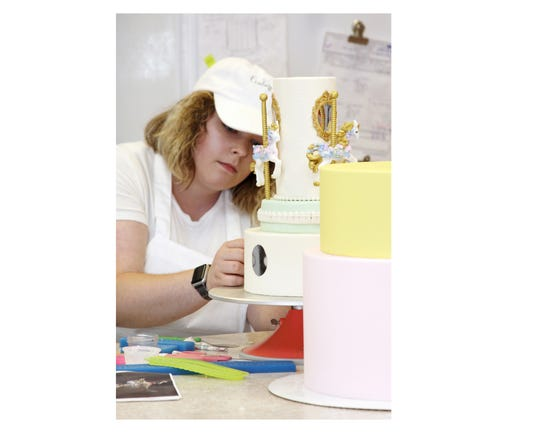 Cake designer Sandy Lesley adds the finishing touches to a carousel-shape cake.
