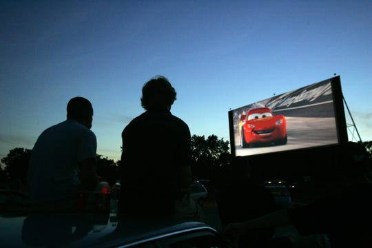 "In this 2006 photo, Jon Martin and Keith Sorgius sit atop their vehicle as they watch the movie, ""Cars,"" at the Tibbs Drive-In on June 16, 2006."