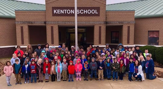 Snuggled in their coats, Kenton Elementary School students and staff take a picture in front of the school.
