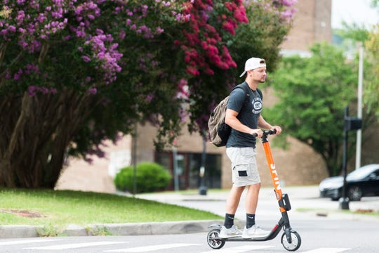 A person scoots down Gay Street on a Spin scooter Thursday, July 11, 2019.