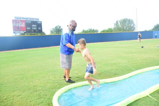 Head coach Matt Hurley gives Sawyer Corum, 8, a helping hand after he practices a slide into home base on a Slip and Slide. 7/11/19