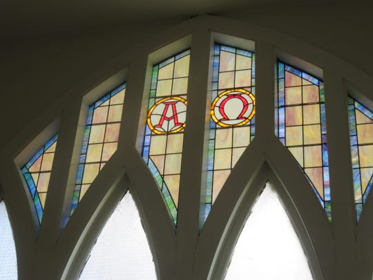 Alpha and Omega stained-glass windows remain.