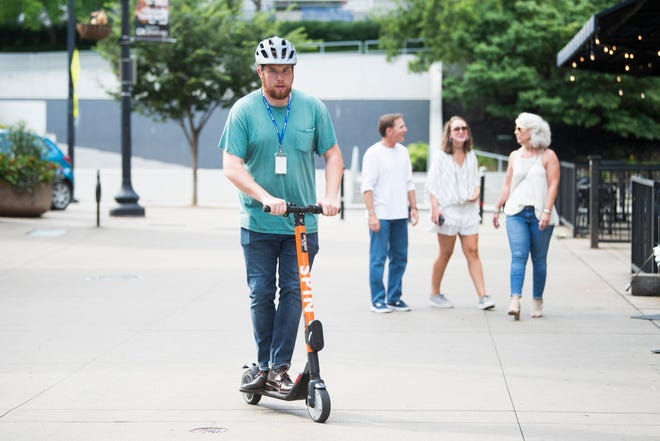 News Sentinel reporter Ryan Wilusz scoots through Market Square on a Spin scooter Thursday, July 11, 2019.
