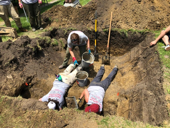 Researchers from the University of Indianapolis work June 28, 2019, at the Fowler Cemetery to undercover the grave of an unidentified woman who was found killed and stuffed in a cardboard box along County Road 200 South in Benton County. The Benton County coroner ordered that the body be exhumed, reopening a case that has never been solved.