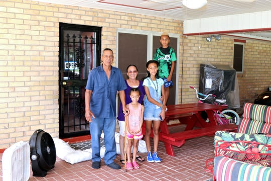 The Biagas family is prepping for a possible hurricane at their home on Terry Drive, which saw flooding in 2016, with sandbags around a storage building and their back door.  Joseph and Helen Biagas stand with grandchildren (from left) Kirah, Makayla and Joseph.