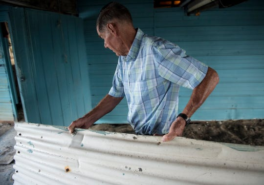 Lee Morvant clears the area underneath his fish camp in Isle de Jean Charles, La., on Friday, July 12, 2019. Isle de Jean Charles is slowly shrinking due to rising sea levels.