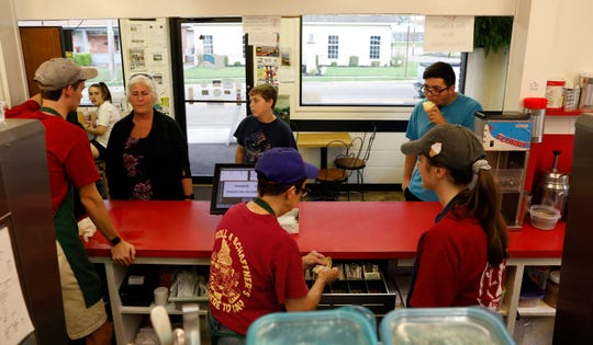 Graham Schaffner, left, Pam Whittington, center, and Morgan Stahl work behind the counter Thursday evening, July 11, 2019, at Schaffner's Drive In in Baltimore.