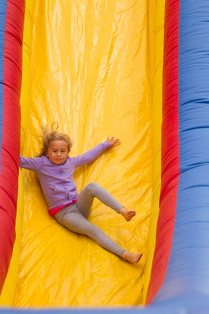 6-year-old Ana Dervishaj slides down the Cliff Hanger inflatable slide provided by Bouncers and More Friday, July 12, 2019 at the Taste of Brighton.