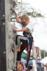6-year-old Austin Slusarzyk scales a climbing wall provided by Bouncers and More at the Taste of Brighton Friday, July 12, 2019.