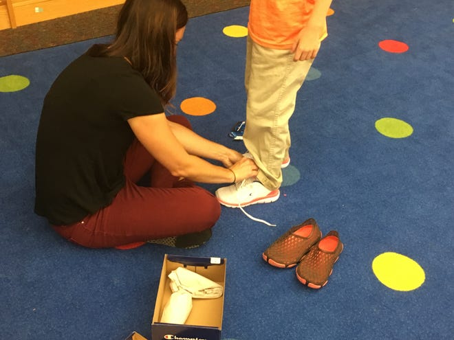 Ashley Knuth ties a pair of new shoes donated through New Kicks for Kids in spring 2019.