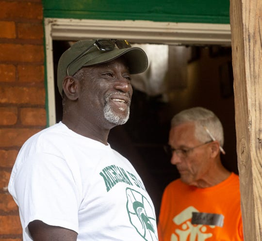 Deon Halliman smiles as he watches volunteers prep the front door being replaced, Wednesday, July 10, 2019 in Lansing, Michigan as part of Rock the Block, a revitalization program through Habitat for Humanity.