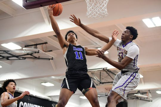 IMG Academy Ascenders forward Jaden Springer (11) drives the ball to the hoop past Montverde Academy Eagles forward Omar Payne (13) during a high school basketball game in April 2019.