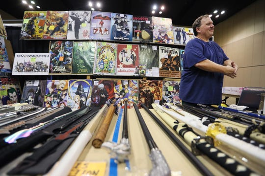 Wes Tillander of Posters, Swords and Comics interacts with customers during Anime Blues Con at the Memphis Cook Convention Center downtown on Friday.