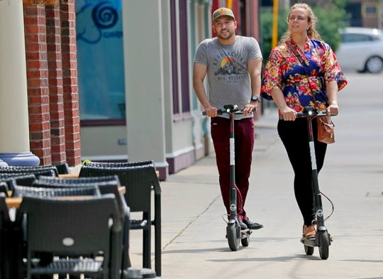 A couple rides their bird scooters down Brady St. in Milwaukee on Monday, July 16, 2018.
