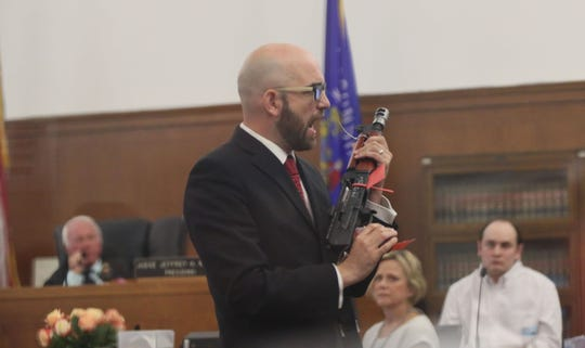 Milwaukee County Assistant District attorney Grant Huebner holds the AK-47-style pistol that was used in the shooting of Milwaukee Police Officer Matthew Rittner as he questions Jordan Fricke, right, on how he used it during the shooting.
