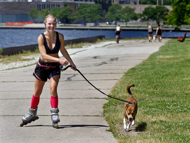 Kathryn Minster, 24, of Mequon enjoys skating with her 2-year-old dog, Shelly, on Thursday at the Milwaukee lakefront. Areas right along the Great Lakes are forecast to be the only places in Wisconsin where some relief might be found as a heat wave takes hold across much of Wisconsin during the coming week.