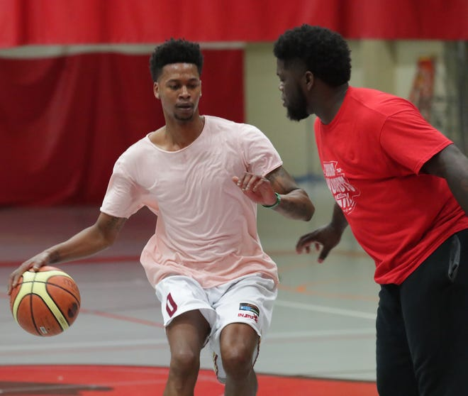 Bryquis Perine dribbles against trainer Thomas Shumpert. Perine, a former Milwaukee Vincent star, has played professionally all over the world.