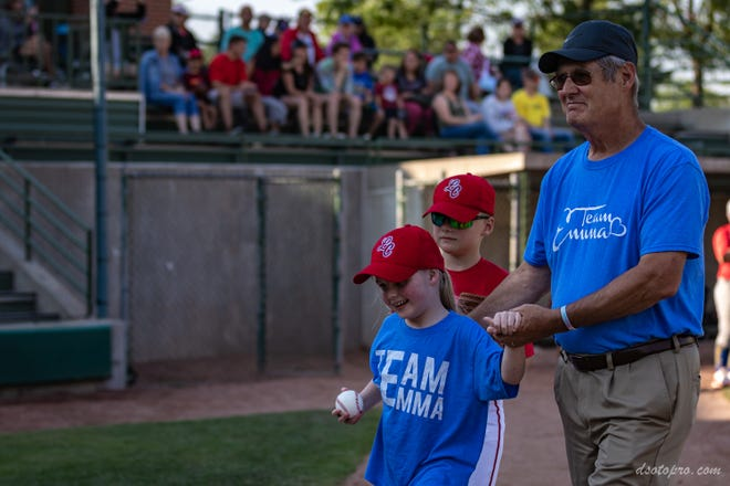 Emma Mertens (with baseball), a 7-year-old from Hartland, threw out the first pitch at her brother's baseball game at Helfaer Field a day after emergency surgery.