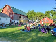 Visitors enjoy Flying Cow Pizza on the lawn at the Mapleton Barn in Oconomowoc on Thursday, July 11, 2019.