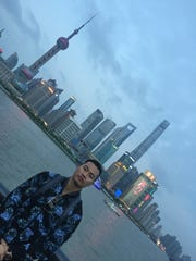 Montgomery native Bao Pham is shown with the Shanghai, China skyline behind him. Pham moved to Shanghai with his family in 2018.