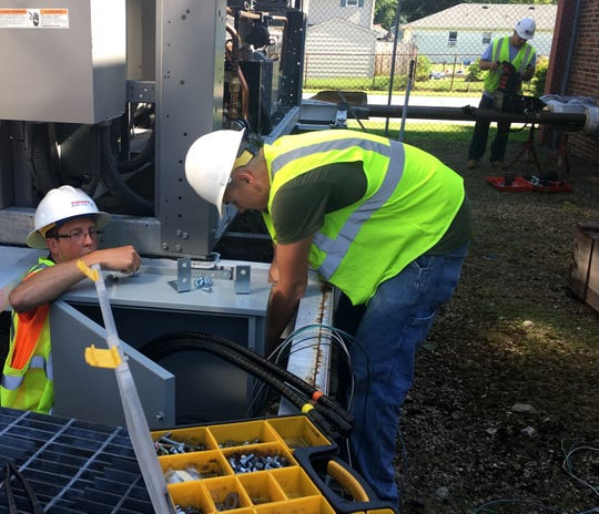 Workers install a new air-cooled chiller at Grissom Elementary School.