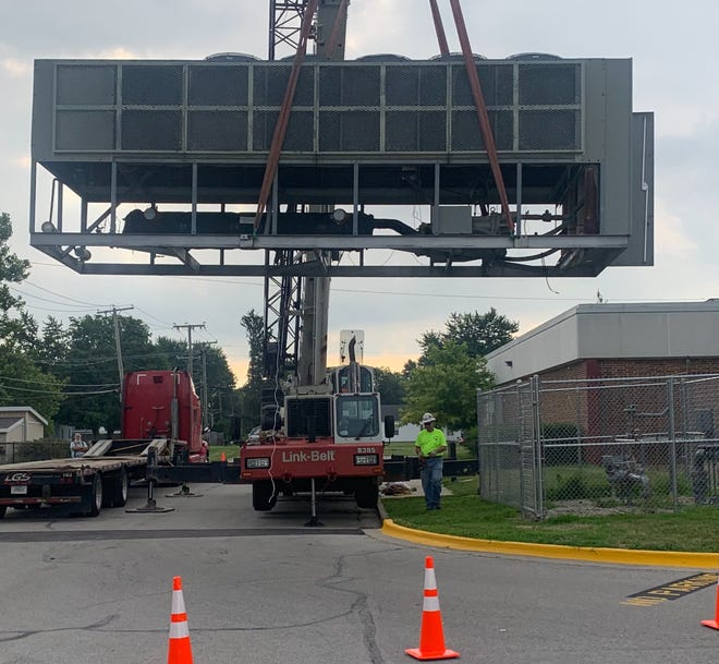 A new air-cooled chiller is crane-lifted into place at Grissom Elementary School.