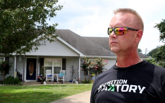 James Fuller, a neighbor of Dylan Scott Levesque, stands in front of Levesque's home were Levesque's 3-year-old son, Daylin Palmer, died after being left in a car in Smyrna on Thursday. Levesque is being charged with of aggravated child abuse and neglect.