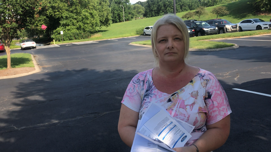 "Carrie Armstrong, of Hendersonville, stands by her 2015 Ford Focus Hatchback. Since she bought it, she's had to take it in for transmission issues ""at least"" three times a year, she said. She spoke with the Tennessean holding a stack of some of her Ford receipts."