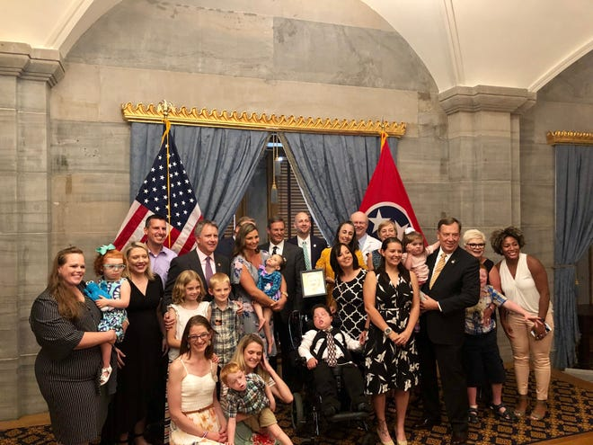 Rep. Sam Whitson stands with families that will benefit from the Katie Beckett waiver, including Zoey Goddard, who Whitson holds with mother Tori standing beside them.