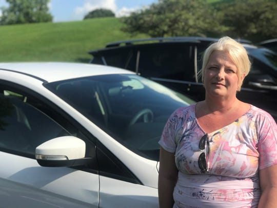 "Carrie Armstrong, of Hendersonville, stands by her 2015 Ford Focus Hatchback. Since she bought it, she's had to take it in for transmission issues ""at least"" three times a year, she said."