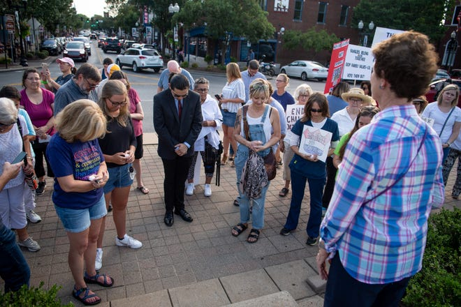Demonstrators gather to pray during a vigil in support of immigration rights at Public Square in Franklin on Friday.