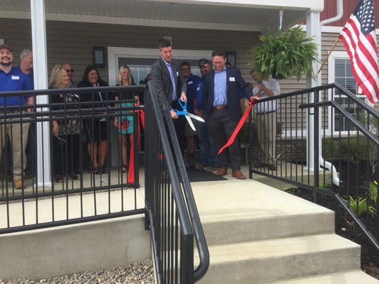 Jonathan Wilcox cuts the ribbon, officially opening the Residences of Heritage Town Center in Pataskala.