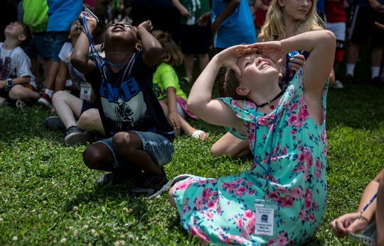 Braylon Hamilton and Olivia Phillips cover their eyes as they search the sky for the rockets they built and launched at Par Excellence Academy. Par Excellence partnered with Owens Corning, Boeing and OSU-Newark to commemorate the anniversary of the Apollo 11 launch.