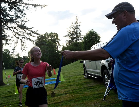 Newark freshman Megan Rosengarten finishes the race and accepts her medal from Jeff O'Brien during the first Bryn Du Summer Cross Country Series race held on Thursday, July 11, 2019.